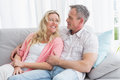 Happy couple relaxing on the couch smiling at each other home in living room Stock Photo