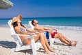 Happy couple relaxing on deck chair at the beach Royalty Free Stock Photo