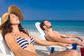 Happy couple relaxing on deck chair at the beach a sunny day Royalty Free Stock Photos