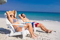 Happy couple relaxing on deck chair at the beach a sunny day Stock Image