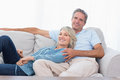 Happy couple relaxing at home on the couch looking camera Royalty Free Stock Image