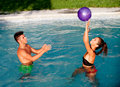 Happy couple relaxing in the pool playing with a ball summer Stock Photos