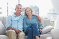 Happy couple relaxing on their couch smiling at camera at home in the sitting room Royalty Free Stock Photography