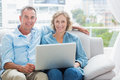 Happy couple relaxing on their couch using the laptop smiling at camera at home in sitting room Royalty Free Stock Images