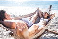 Happy couple relaxing together in the hammock and smiling at each other beach Stock Photo