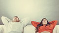 Happy couple relaxing yawning on couch at home smiling young and yawing calm carefree men and women resting with arms behind head Royalty Free Stock Photos