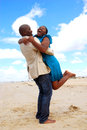 Happy couple reunion an african american young woman jumping into the arms of her black spouse for a on the beach Stock Image
