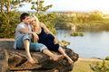 Happy couple romantic date on nature sit aloft on rock with beautiful view Stock Photos