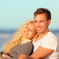 Happy couple romantic lovers relaxing at beach sunset sitting down resting young men and women enjoying romance honeymoon Stock Image