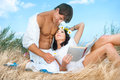 Happy couple romantic young reposing at grass against sky background Royalty Free Stock Photo