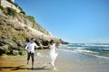 Happy couple running on the beach near sea in wedding day Royalty Free Stock Photo