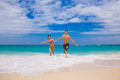 Happy couple running on the beach sea in background Royalty Free Stock Photography