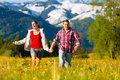 Happy couple running grass front mountain panorama Royalty Free Stock Photography