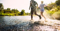 Happy couple running in shallow water Royalty Free Stock Photo