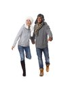 Happy couple running at wintertime mixed wearing warm clothes Royalty Free Stock Image