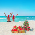 Happy couple in santa hats at sea beach near christmas tree Royalty Free Stock Photo