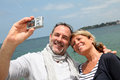Happy couple on the seaside taking selfie retired picture of themselves by sea Royalty Free Stock Photography