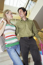 Happy Couple With Shopping Bags In Mall Stock Image
