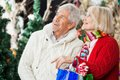Happy couple shopping at christmas store senior with bags looking up Stock Photo