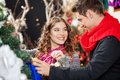 Happy couple shopping for christmas tree young looking at each other while in store Royalty Free Stock Image
