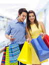 Happy couple in shopping mall surprised men peeking into bag Stock Images
