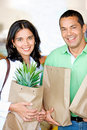 Happy couple shopping in supermarket with bags Royalty Free Stock Photos