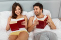 Happy Couple Sitting in Bed Reading Books at Home Royalty Free Stock Photo
