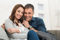 Happy couple sitting on couch embracing looking at camera Stock Photography