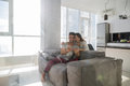 Happy Couple Sitting On Couch Using Tablet Computer Modern Apartment With Panoramic Window Royalty Free Stock Photo