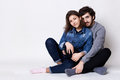 A happy couple sitting crossed legs on the floor. A bearded guy embracing her girlfriend with love. Two people sitting close to ea Royalty Free Stock Photo