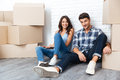 Happy couple sitting on floor around boxes after buying house Royalty Free Stock Photo