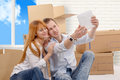 Happy couple sitting on the floor taking selfie in their new hou a house Stock Images