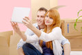 Happy couple sitting on the floor taking selfie in their new hou a house Royalty Free Stock Images