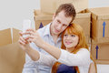 Happy couple sitting on the floor taking selfie in their new hou a house Stock Photography