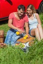 Happy couple sitting on the grass having picnic together a sunny day Stock Photos