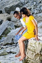 Happy couple sitting at rocky shore Stock Images