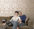 Happy couple sitting on sofa portrait of Stock Image
