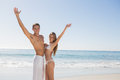 Happy couple smiling at camera and waving on the beach Royalty Free Stock Images