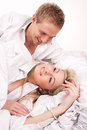 Happy couple smiling lying in bed Royalty Free Stock Photo
