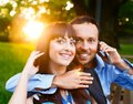 Happy couple smiling middle aged with mobile phone outdoors Stock Photo