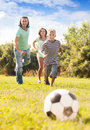 Happy couple with son playing with soccer ball at summer park Royalty Free Stock Image