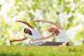Happy couple stretching and doing yoga exercises fitness sport people concept on mats over green tree leaves background Stock Image
