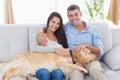 Happy couple stroking dog while sitting on sofa