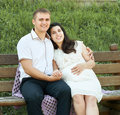 Happy couple in summer city park outdoor, pregnant woman, bright sunny day and green grass, beautiful people portrait, yellow tone Royalty Free Stock Photo