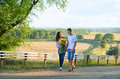 Happy couple with sunflowers having fun and walking along country road outdoors - romantic travel, hiking, tourism and people conc Royalty Free Stock Photo