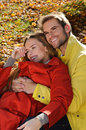 Happy couple in sunny autumn park fall young family having fun outdoors yellow trees and leaves laughing man and woman outside Stock Photos