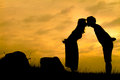 Happy couple on sunset rock silhouette a field two stones and two people Stock Photos