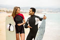 Happy couple with surf boards cheerful adult running on the beach Royalty Free Stock Image