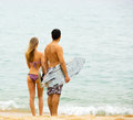 Happy couple with surf boards cheerful running on the beach Stock Photos