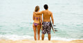 Happy couple with surf boards running on the beach Stock Photography